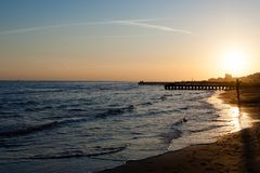 Beach landscape at dawn. Piers perspective view with people. Jesolo beach view. Italian panorama stock images