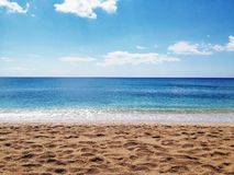 Beach landscape. Ocean with blue and green water and land in the distance Royalty Free Stock Photography