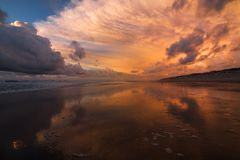 Beach landscape in Portugal at sunset - sky and clouds reflections stock photography