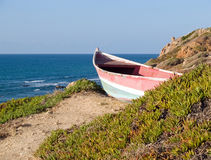 Beach landscape - Skiff boat on the cliff. Beach coast  landscape - small colorful skiff dory boat on the cliff Stock Photography