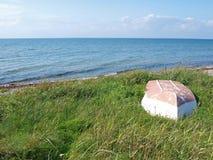 Beach landscape -Skiff boat on the grass Stock Photo