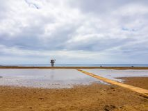 Beach landscape and wooden footbridge to reach the coast with lifeguard post and green flag allowing swimming. Canary Islands,. Spain water tracks morning wet stock photography