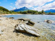 Beach of Lapataia Bay in Terra del Fuego National Park, Patagonia, Argentina. Stones on beach of Lapataia Bay with mountains in background, Terra del Fuego stock photo
