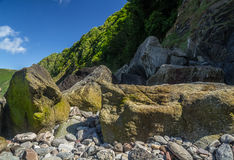 Beach with large boulders at low tide Stock Images