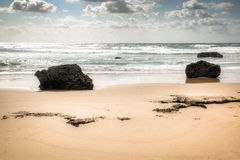 Beach with large rocks in Tofo. Very rustic and empty beach with large rocks at the Indian Ocean in the coastal town Praia do Tofo in Inhambane, Mozambique Stock Image