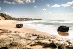 Beach with large rocks in Tofo. Very rustic and empty beach with large rocks at the Indian Ocean in the coastal town Praia do Tofo in Inhambane, Mozambique Royalty Free Stock Photo
