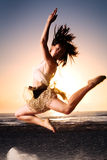 Beach leap. Woman leaps on beach at sunrise Royalty Free Stock Image