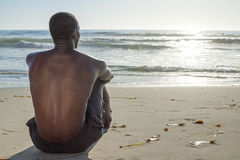 Beach life. Back view of lean young shirtless African American man sitting on sand while watching waves roll in on beautiful beach under setting sun Stock Images