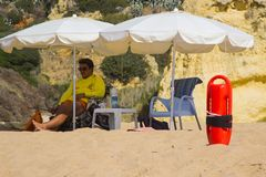 A beach life guard under the shade of his sun brolly while scanning the beach in Albuferia in Portugal. A beach life guard under the shade of his sun brolly Royalty Free Stock Photos