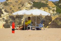 A beach life guard under the shade of his sun brolly while scanning the beach in Albuferia in Portugal. A beach life guard under the shade of his sun brolly Royalty Free Stock Photography