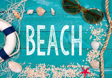 Beach Life - Happy Holidays. Beach utensils on turquoise wooden background with text stock image