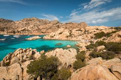 Beach life at Spiaggia Cala Coticcio. Beach life with people sitting on rocks at Spiaggia Cala Coticcio on the Italian island of Caprera royalty free stock image