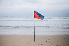 Beach lifeguard high hazard flag. Photo of high hazard red and blue flag on stormy windy beach cautioning surfers and tourists not to enter ocean sea waters stock photography
