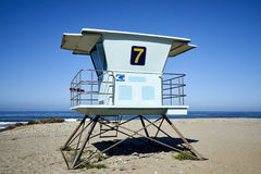Beach lifeguard tower on the California coastline against blue skies. Washed out blue lifeguard post guarding a stretch of Pacific Ocean beach in Ventura stock photo