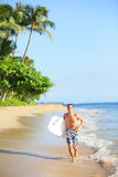 Beach lifestyle man surfer with surfing bodyboard. Running in water on tropical beach. Handsome male model in swimwear having summer vacation holidays fun on Stock Photography