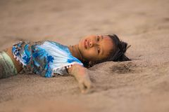 Beach lifestyle portrait of young beautiful and happy Asian American mixed ethnicity child girl 7 or 8 years old playing lying on. The sand having fun enjoying royalty free stock images