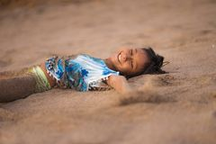 Beach lifestyle portrait of young beautiful and happy Asian American mixed ethnicity child girl 7 or 8 years old playing lying on. The sand having fun enjoying stock photos