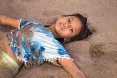 Beach lifestyle portrait of young beautiful and happy Asian American mixed ethnicity child girl 7 or 8 years old playing lying on royalty free stock photos