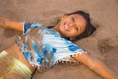 Beach lifestyle portrait of young beautiful and happy Asian American mixed ethnicity child girl 7 or 8 years old playing lying on stock photography