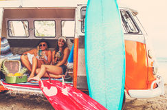Beach Lifestyle Surfer Girls in Vintage Surf Van. Beach Lifestyle. Beautiful Young Surfer Girls Having Fun Hanging Out in Vintage Surf Van. Best Friends Royalty Free Stock Photo