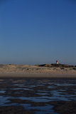 Beach with lighthouse. Tidelands with dunes and a lighthouse Royalty Free Stock Images
