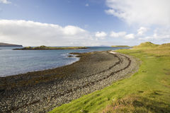 Beach line with blue sky, clouds and green grass. Scotland Royalty Free Stock Photos