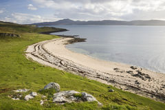 Beach line with blue sky, clouds and green grass. Scotland Stock Image
