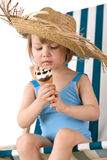 Beach - Little girl on deckchair with ice-cream. Beach - Little girl on deck-chair with straw hat and ice-cream cone Stock Images