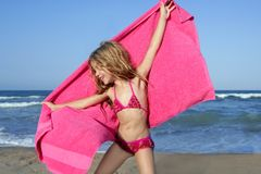 Beach little girl playing pink towel and wind Royalty Free Stock Images