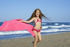 Beach little girl playing pink towel and wind Stock Image