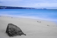 Beach looking to St Ives. Big rock on sandy beach with blue sea and st ives in the background Stock Image