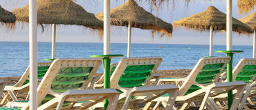 Beach lounge chair and beach umbrella at lonely sandy beach Stock Image