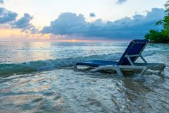 Beach lounge chair in water on beautiful white sand seashore as the light of the skies begin to glow at sunset royalty free stock photography