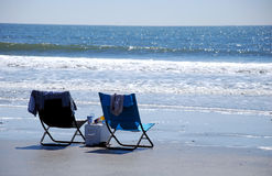 Beach Lounge Chairs. A couple of folding chairs and a cooler sitting right in front of the ocean Stock Photo
