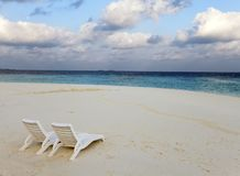 Beach lounge chairs on a beautiful tropical sand beach with cloudy blue sky. Maldives Stock Photography
