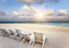 Beach lounge chairs on a beautiful tropical sand beach with cloudy blue sky. Maldives Stock Image