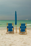 Beach lounge chairs over cloudy sky Stock Image
