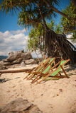 Beach lounge chairs on sandy beach Stock Images