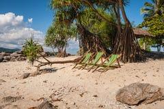 Beach lounge chairs on sandy beach Stock Image