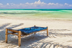 Beach Lounge Chairs under palm tree leaves at the shore of India. N ocean, Zanzibar, Tanzania Royalty Free Stock Image