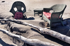 Beach lounge. A cozy beach lounge is being reclaimed by the sand after a storm Stock Photo