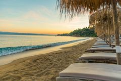 Beach lounge at sunset. Sunset at the beach with lounge chairs and reed umbrellas, Skiathos island, Greece, 2018 royalty free stock photography