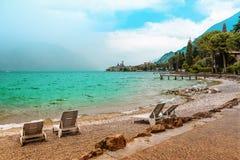 Beach lounger at lake shore gardasee with wavy water, malcesine. Beach lounger at lake shore gardasee with wavy water, tourist destination malcesine italy Stock Photography