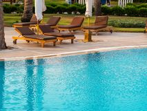 Beach lounger, sun lounger near the pool with turquoise water stock images