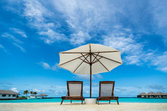 Beach lounger and umbrella on sand beach. Royalty Free Stock Photography