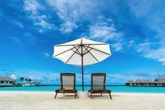 Beach lounger and umbrella on sand beach. Stock Photos
