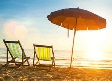 Beach loungers on deserted coast sea at sunrise. stock photography