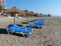Beach Loungers and Huts, Malaga Beach, Spain. Blue Beach Loungers and Huts, Malaga Beach, Spain Stock Photos