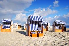 Beach loungers, sea coast, sunny beach,Kolobrzeg,Polska. Beach baskets are standing on a sandy beach and waiting for tourists, the Baltic coast on a beautiful royalty free stock photography