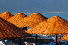 Beach loungers and umbrellas Stock Photos